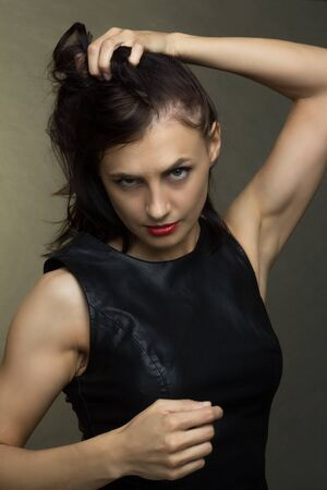a brunette in a black leather sleeveless blouse poses on a gray background