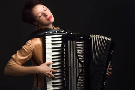 A brunette in a gold shirt, with a short haircut, on a dark background of the Studio. play the accordion