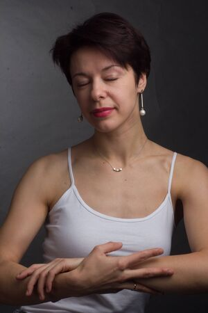 brunette with short hair. Studio portrait in white t-shirt. arms are crossed at chest level 免版税图像