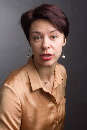 brunette with short hair. Studio portrait in a yellow blouse. a surprised, shocked expression