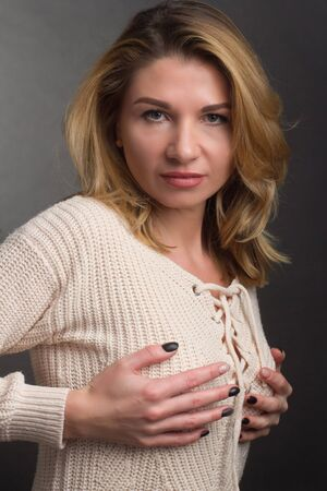 Portrait of a middle aged blonde woman in white clothes on a light gray background. keeps hands on the chest