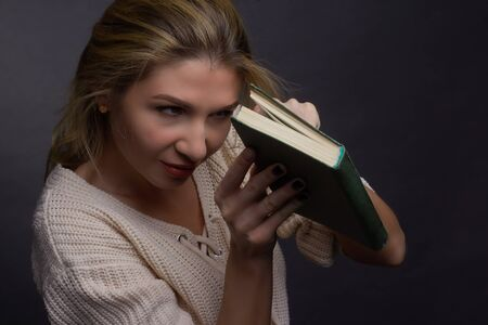 Portrait of a middle aged blonde woman in white clothes on a light gray background. he look in half-open book. concept of adult education