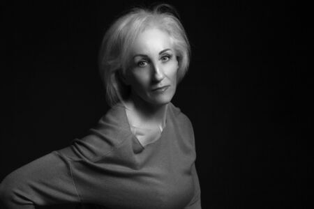 Classic black-and-white dramatic portrait of elderly blonde woman in Studio on black background