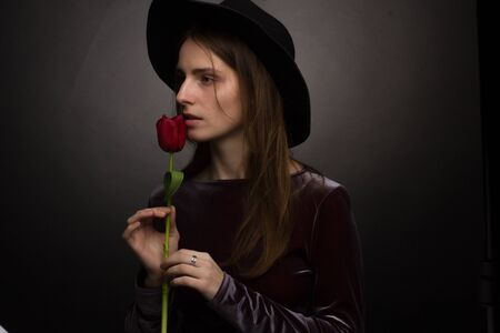 The girl in the purple dress and wide-brimmed black hat on a dark background in the Studio with a red Tulip flower in the hand . creative portrait of a sensual woman Imagens