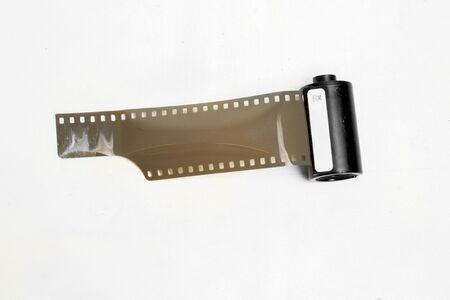 vintage photographic film with perforations in the cassette on white background isolate