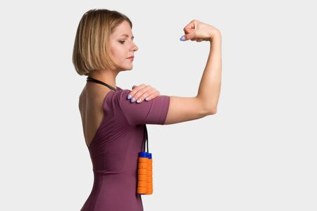 Young Fitness woman in training dress. With a rope. Isolate white background. shows biceps
