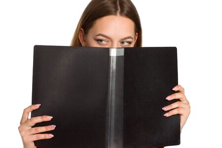 A young business woman against a white background isolated. hiding behind an office folder Banque d'images