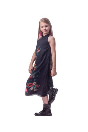 child girl with long hair. In a black dress with a flower pattern on a light gray Studio background. in jump motion, flying hair