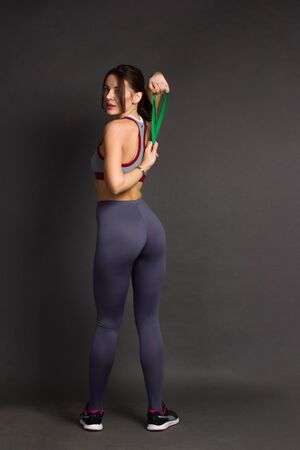 young woman is engaged in fitness In sportswear with elastic band. photo on grey background