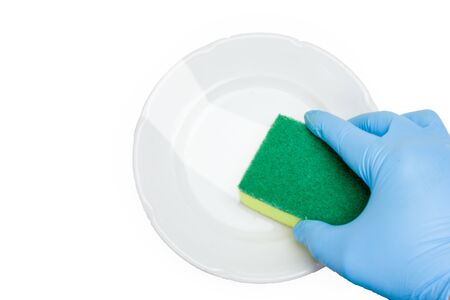 A hand in a blue rubber glove washes a white plate. Isolate on a white background. The view from the top