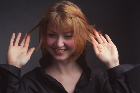 Studio portrait of a young funny woman with short hair in a black blouse, laughing, disheveled hair