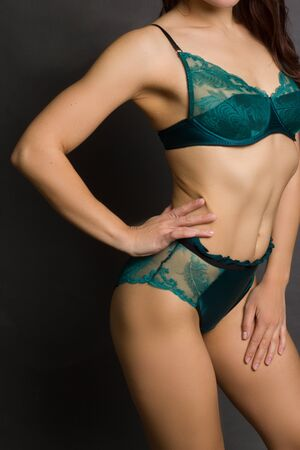 Unrecognizable fit woman, stands with his back, in green lingerie. Body care, healthy and sporty life concept
