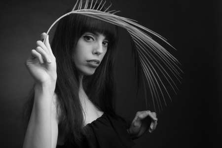 black and white portrait of brunette with long hair, off shoulder, holding a palm leaf