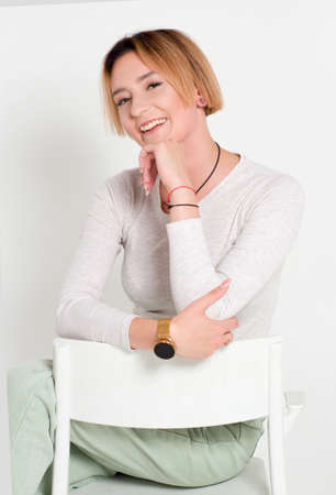 Portrait of a young woman with short hair. In a white sweater and green trousers. On white background. sitting on a white chair