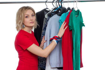 a blonde girl with short hair on a white background, an isolate in a red dress, chooses clothes hanging on a hanger. The concept of shopping, sales or fitting clothes fashionista,