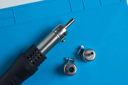 Hot air gun for soldering, and additional attachments to it, on the background of a blue mat