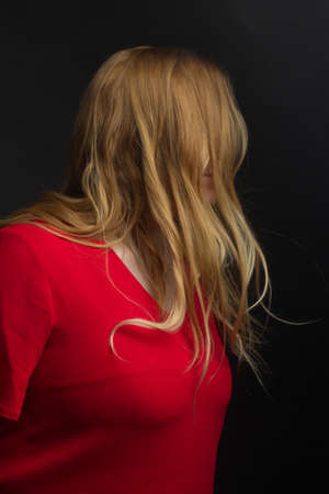 a blonde girl with an overweight plus size, in a red overall posing on a dark Studio background. she turned away from the camera