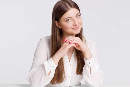 A pretty brunette with a chin on her hands is sitting at a desk 免版税图像