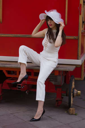 A young, beautiful and slender brunette, with long hair, wearing a white hat and a pantsuit, next to a red carriage 免版税图像