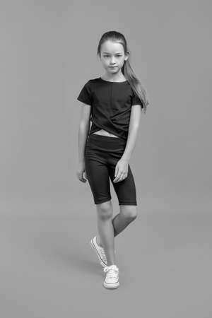 Black and white Studio portrait of a young girl with brown hair, with long hair, on a gray background in a black T-shirt and shorts