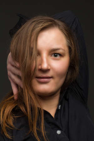 A young brown hair woman who is overweight. Photo dark in the studio