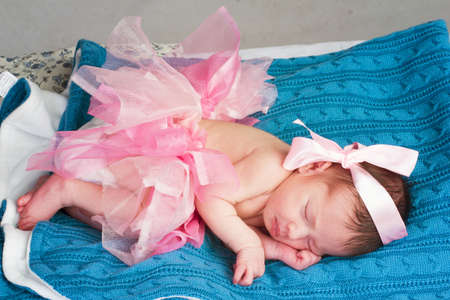 photo of a baby girl in a pink skirt and bow. On the blue blanket