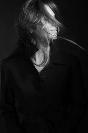 Black and white portrait of a young girl with long hair in a studio on a black background