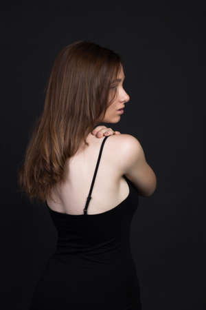 Young brown-haired woman, studio photo on a black background. She stands with her back to me, her arms crossed over her chest.