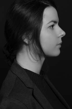 Black and white portrait of a young brunette woman in profile, in a studio on a black background