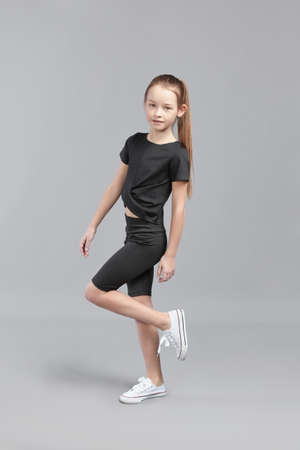 Studio portrait of a young girl with brown hair, with long hair, on a gray background in a black T-shirt and shorts 免版税图像