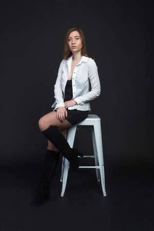 Young brown-haired woman, studio photo on a black background, sitting on a white chair in a white blouse