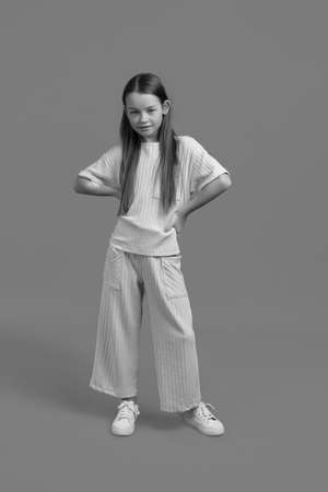 Black and white Studio portrait of a young girl with brown hair, with long hair, on a gray background in white clothes