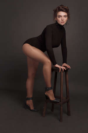 Young brunette woman, with gathered hair hairstyles, in the studio on a black background in a black tight-fitting bodysuit. leans on a bar stool 免版税图像