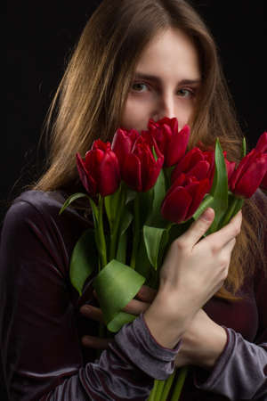 Studio portrait of a young woman on a black background with a bouquet of red tulips in her hands