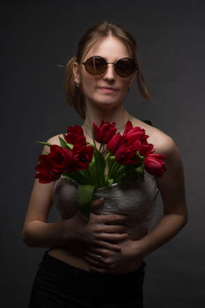 Studio portrait of a young woman in sunglasses, on a black background, with a bouquet of red tulips in her hands 免版税图像