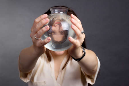 A brunette woman with long hair, wearing a beige blouse on a gray studio background. Looks at the camera through a glass vase