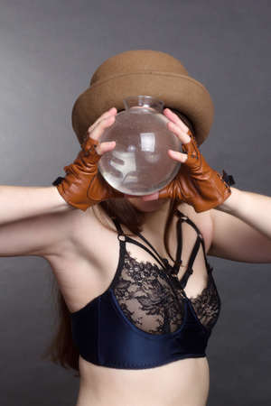 A brunette woman with long hair, wearing a beige blouse, brown hat and gloves on a gray studio background. Looks at the camera through a glass vase