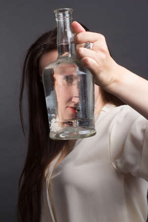 A brunette woman with long hair, wearing on a gray studio background. Looks at the camera through a glass vase