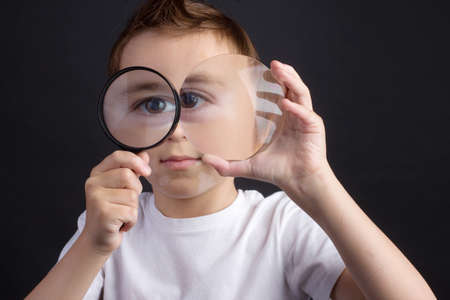 young guy in a white T-shirt looking through a magnifying glass at the camera