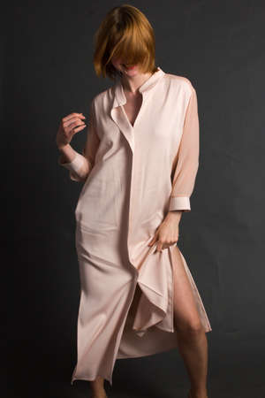 a young blonde woman in a light pink raincoat. Studio portrait on a dark background