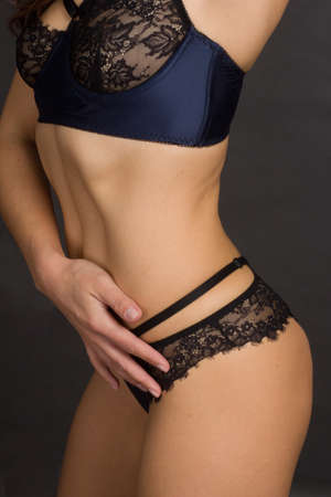 studio shot of a woman's body in blue underwear on a dark background