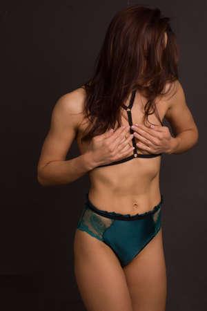 studio shot of a woman's body in green underwear on a dark background