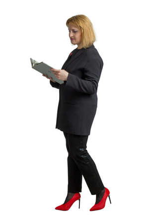 A plump adult woman dressed in a business-like black suit and red shoes. isolated on white. reads a book
