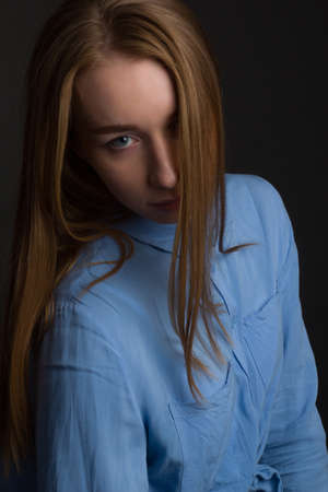 A young woman in blue blouse, a portrait on a black studio background.