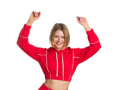 a young fit woman with short hair, wearing a red tracksuit, isolated on a white background. 免版税图像