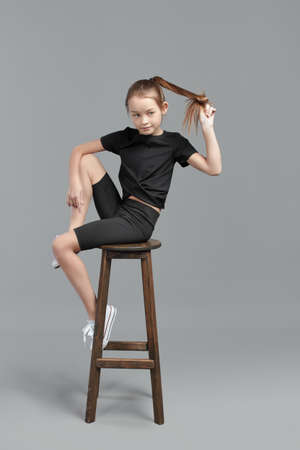 Studio portrait of a young girl with brown hair, with long hair, on a gray background in a black T-shirt and shorts. sitting on a bar stool 免版税图像