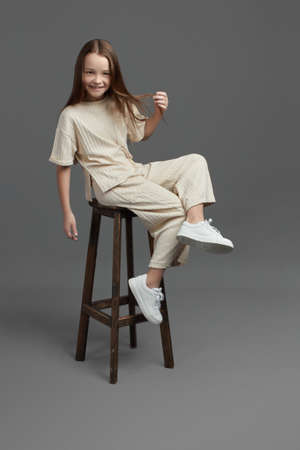 Studio portrait of a young girl with brown hair, with long hair, on a gray background in beige clothes. sitting on a bar stool