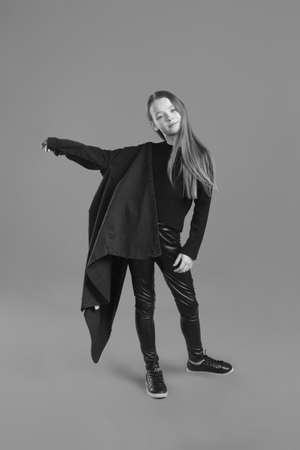 Black and whit Studio portrait of a young girl with brown hair, with long hair, on a gray background in black clothes and a leather jacket