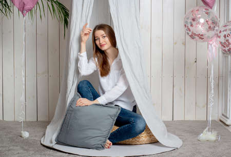 Studio portrait of a young woman with brown hair and long hair, sitting in a tent made of white cloth