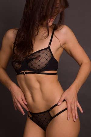 studio shot of a woman's body in black underwear on a dark background